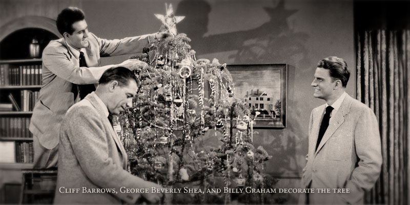 Cliff Barrows (music and program director, Billy Graham Evangelistic Association), George Beverly Shea and Billy Graham trim the Christmas tree.