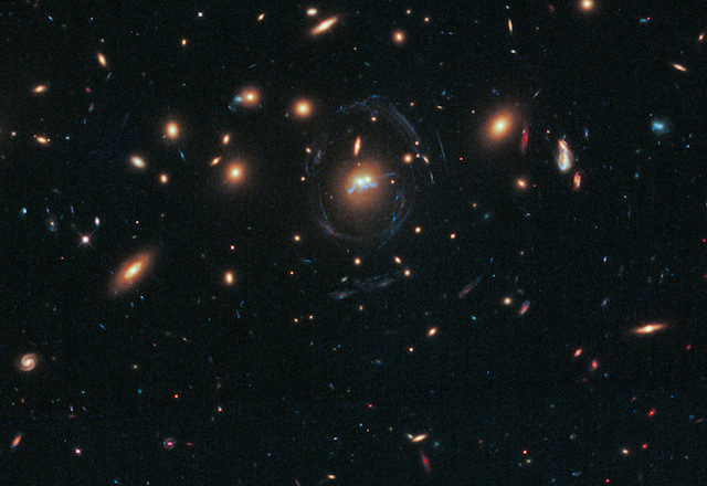 "NASA's Hubble Space Telescope has photographed the dense galaxy cluster SDSS J1531+3414 in the northern constellation Corona Borealis. Made up primarily of giant elliptical galaxies with a few spirals and irregular galaxies thrown in for good measure, the cluster's powerful gravity warps the image of background galaxies into blue streaks and arcs. At the center of the bull's-eye of blue, gravitationally lensed filaments lies a pair of elliptical galaxies that are also exhibiting some interesting features. A 100,000-light-year-long structure that looks like a string of pearls twisted into a corkscrew shape winds around the cores of the two massive galaxies. The ""pearls"" are superclusters of blazing, blue-white, newly born stars. These super star clusters are evenly spaced along the chain at separations of 3,000 light-years from one another. Astronomers first hypothesized that the string of pearls was actually a lensed image of one of the background galaxies. Upon closer inspection, it was revealed that the two elliptical galaxies are in the process of interacting and are beginning to share material between themselves. (Image:NASA/ESA)"